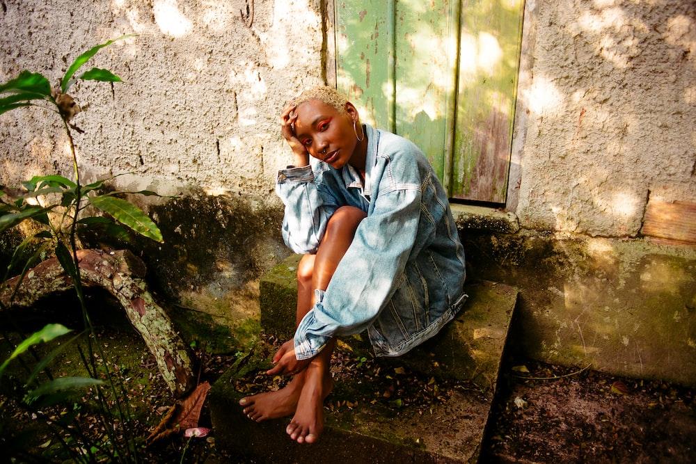 boy in blue dress shirt sitting on brown wooden bench