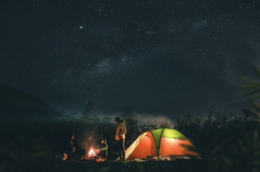 man in green and yellow tent under starry night