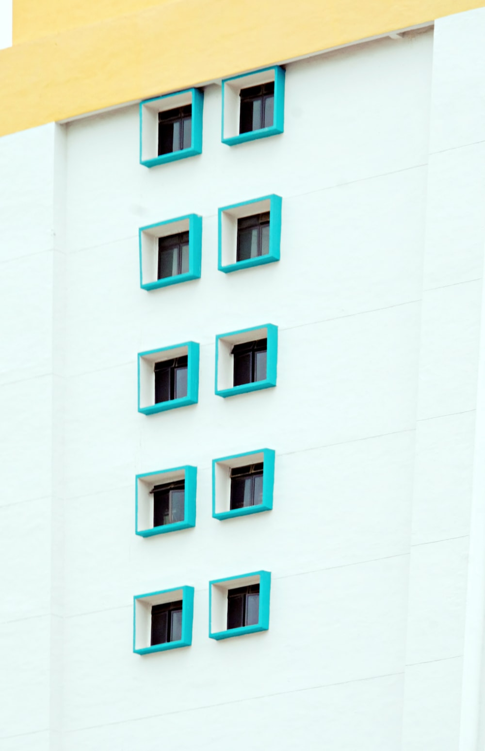 white concrete building with green windows