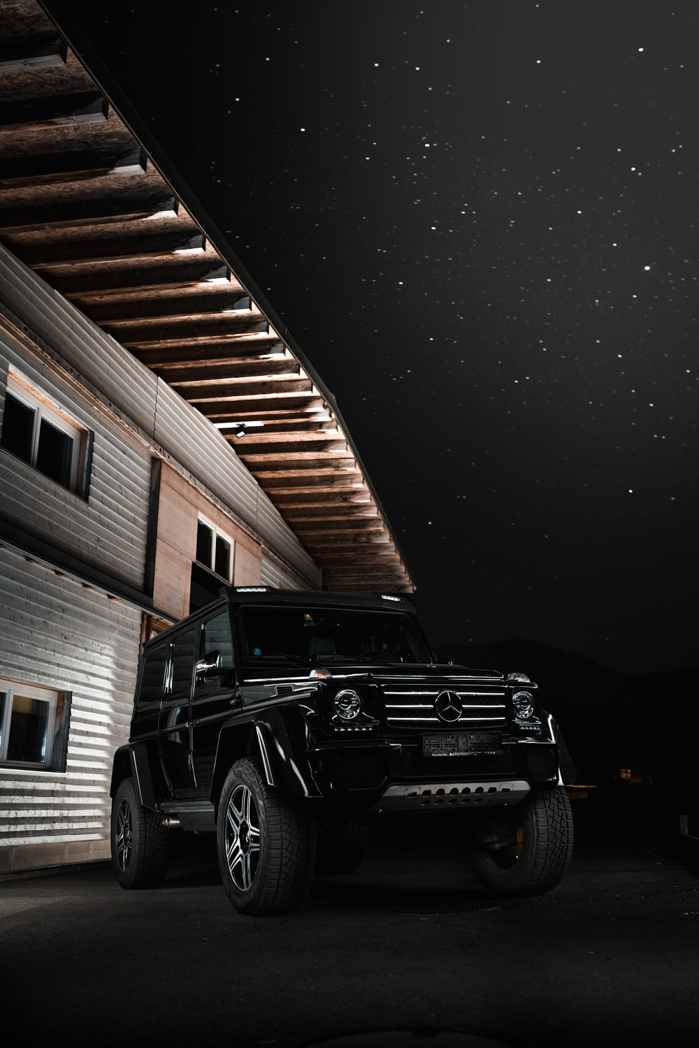 black jeep wrangler parked near brown wooden wall