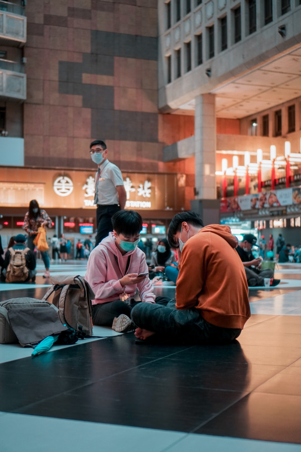 man in red long sleeve shirt sitting on floor