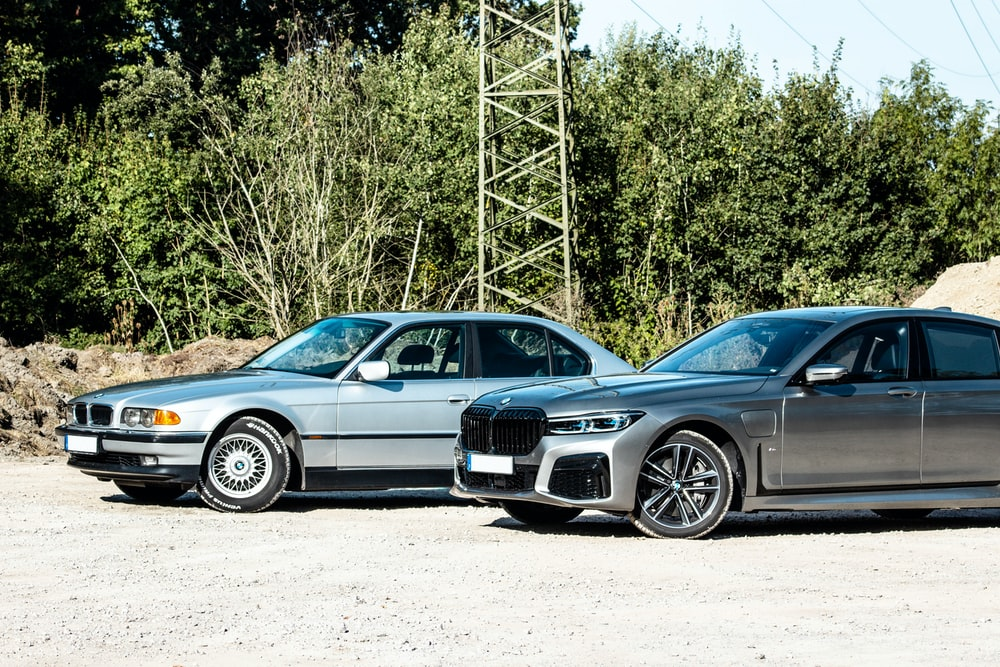 black bmw coupe parked beside gray metal tower during daytime
