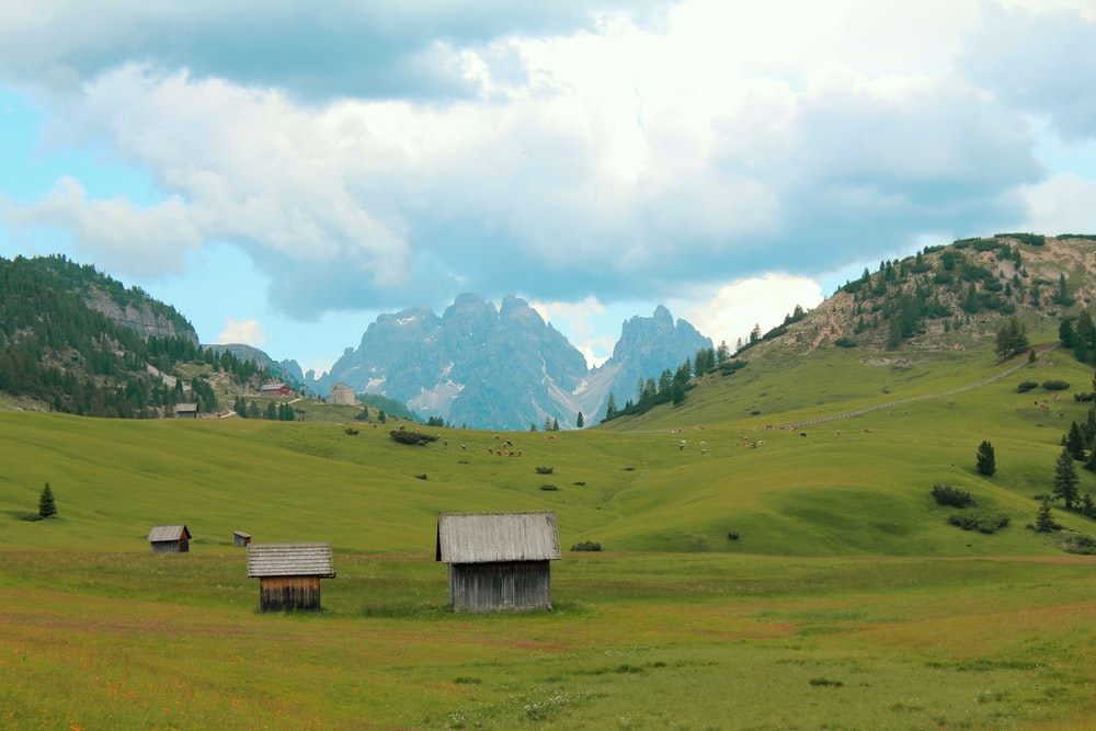 brown wooden house on green grass field near mountains under white clouds during daytime