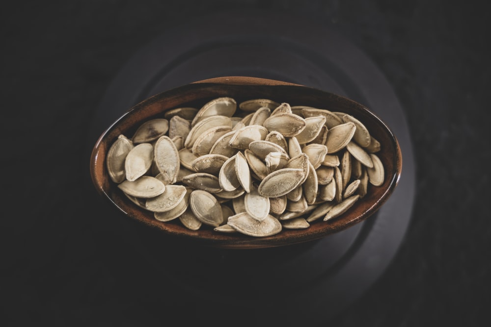 brown and white nuts on brown ceramic bowl