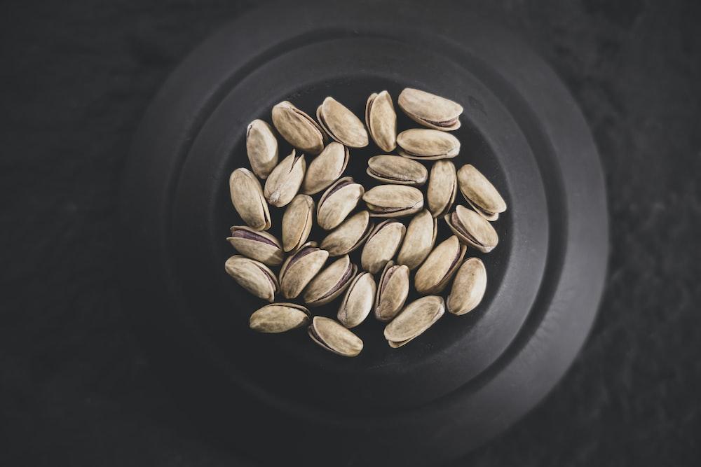 brown coffee beans on black ceramic plate