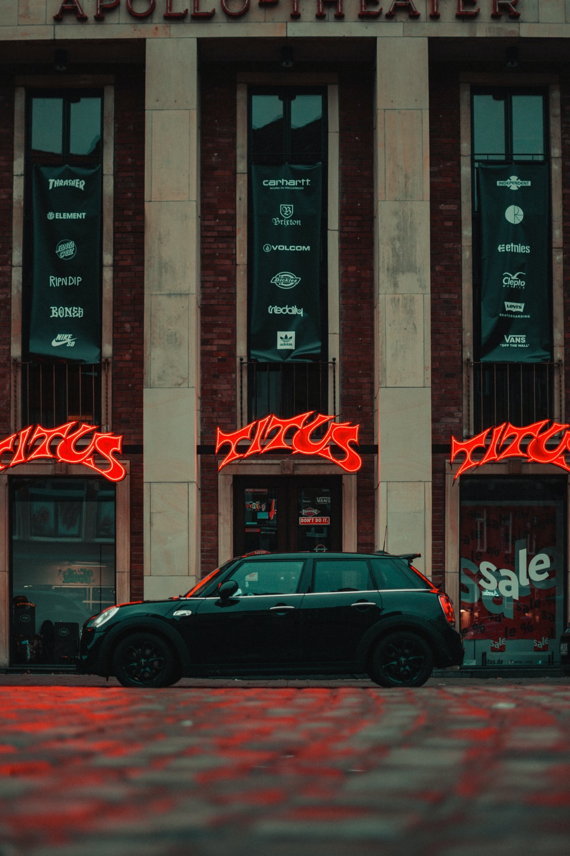 black sedan parked beside brown concrete building during nighttime