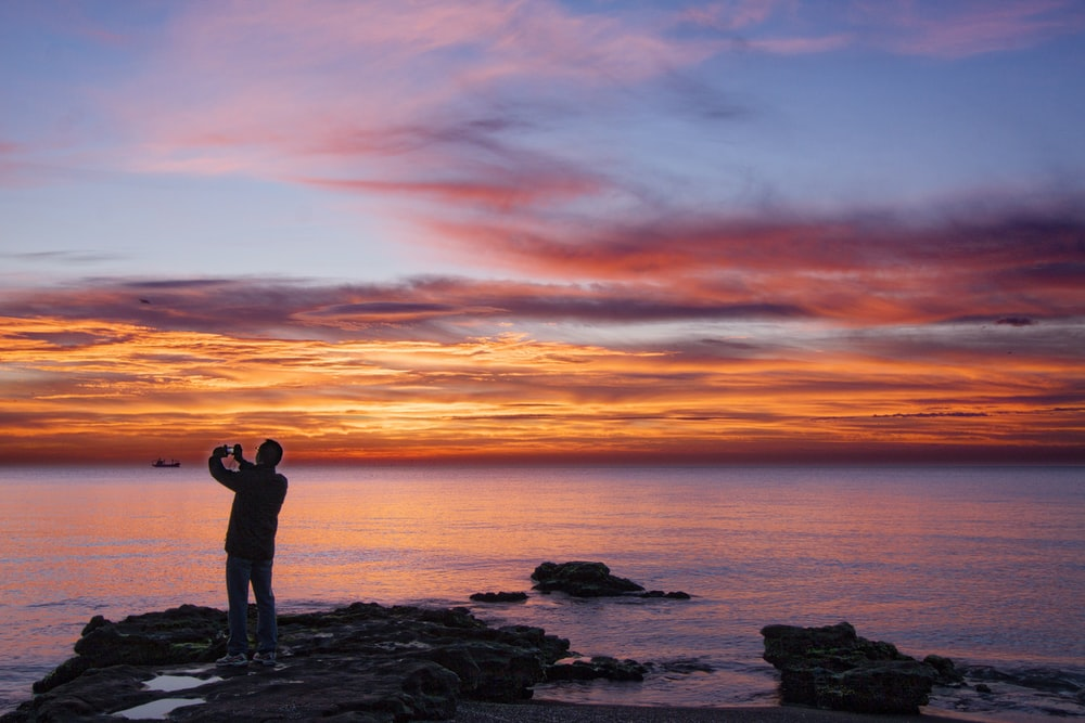 silhouette of woman standing on rock formation near body of water during sunset