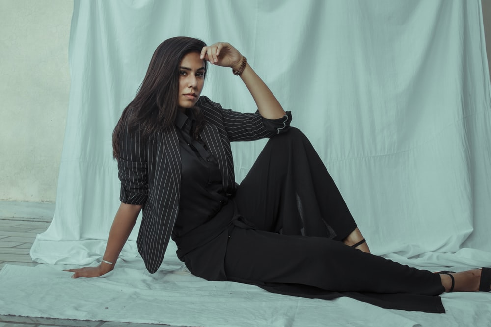 woman in black dress sitting on blue floor