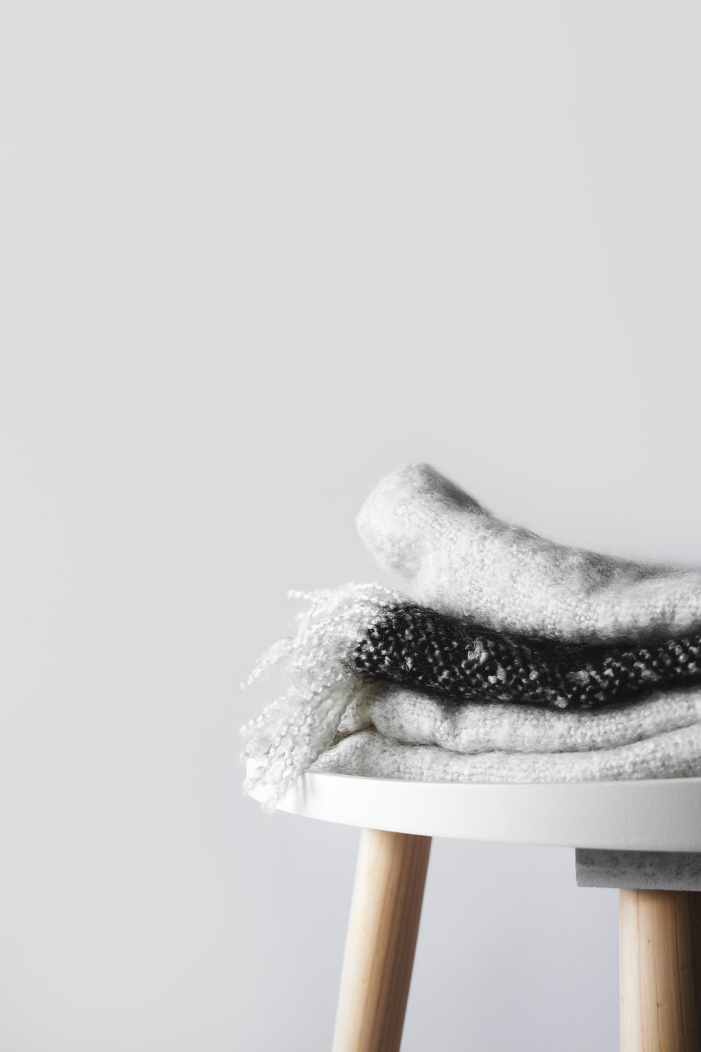 white and black textile on white and brown wooden seat