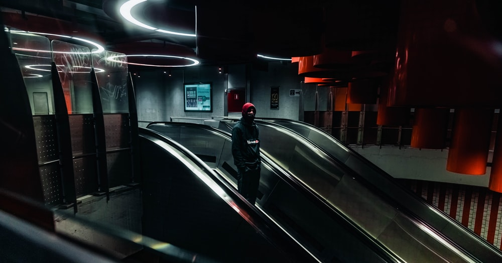 man in black jacket walking on the escalator