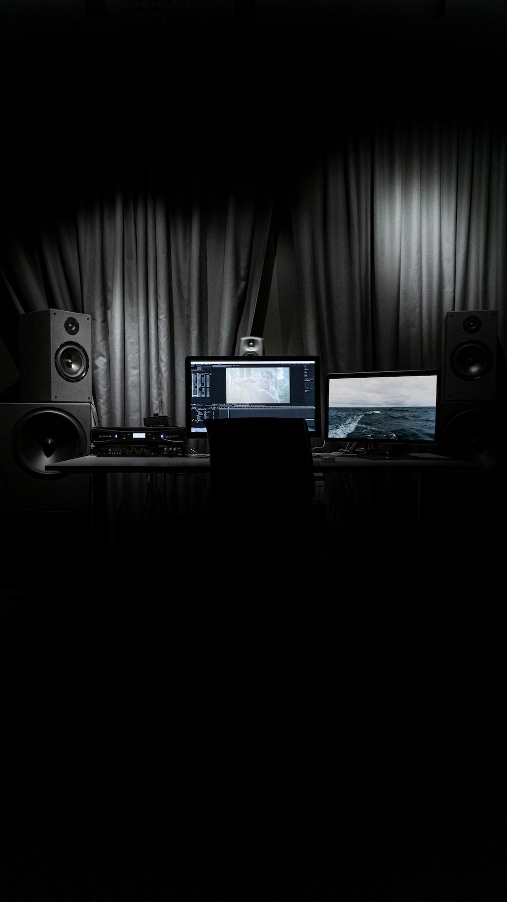 black laptop computer turned on beside black speaker
