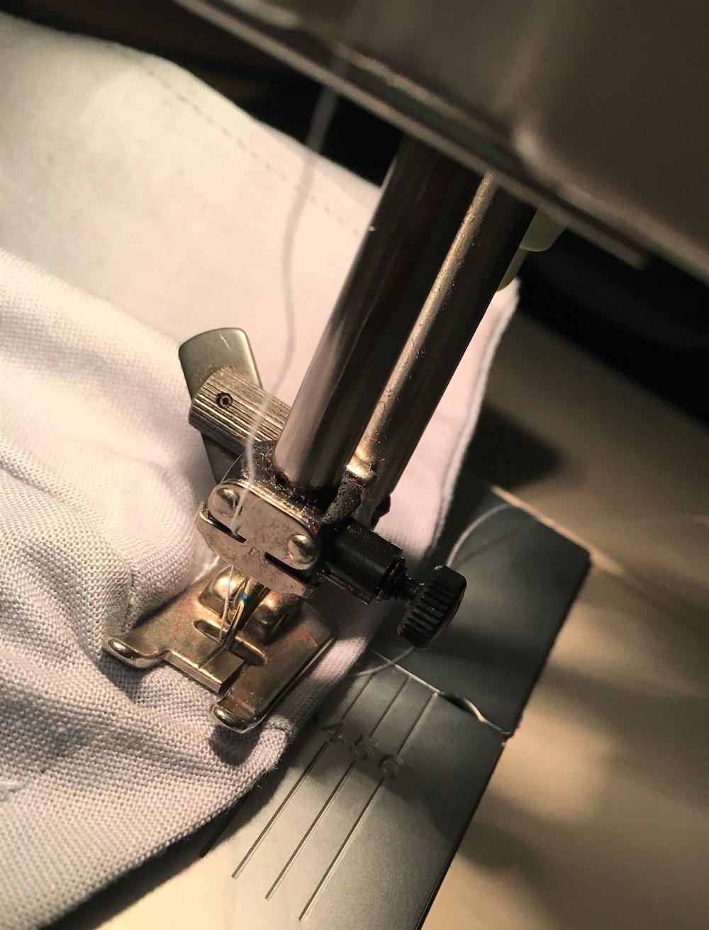 gray metal tool on white textile