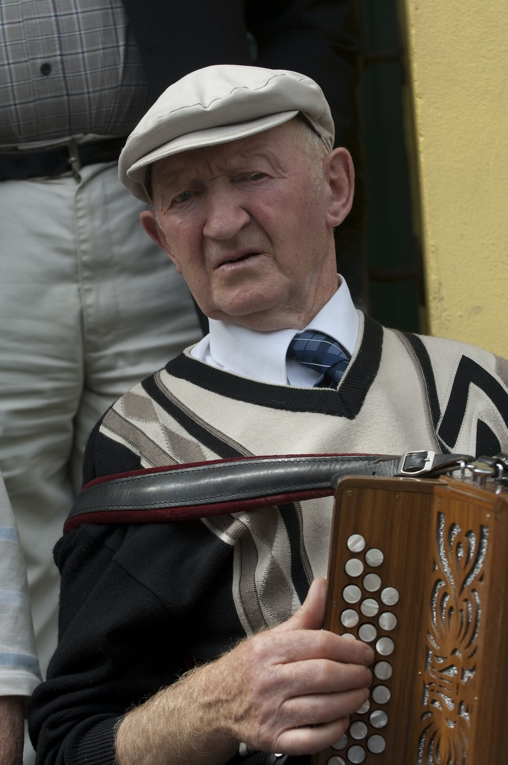 man in black and white striped shirt playing red and black musical instrument