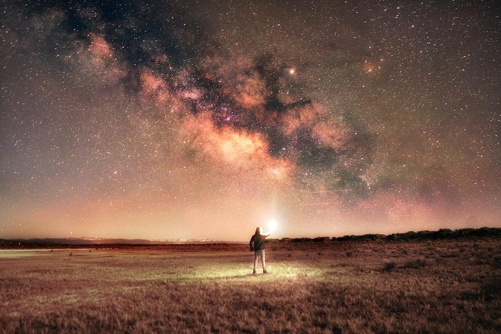 man in white shirt standing on brown grass field under starry night