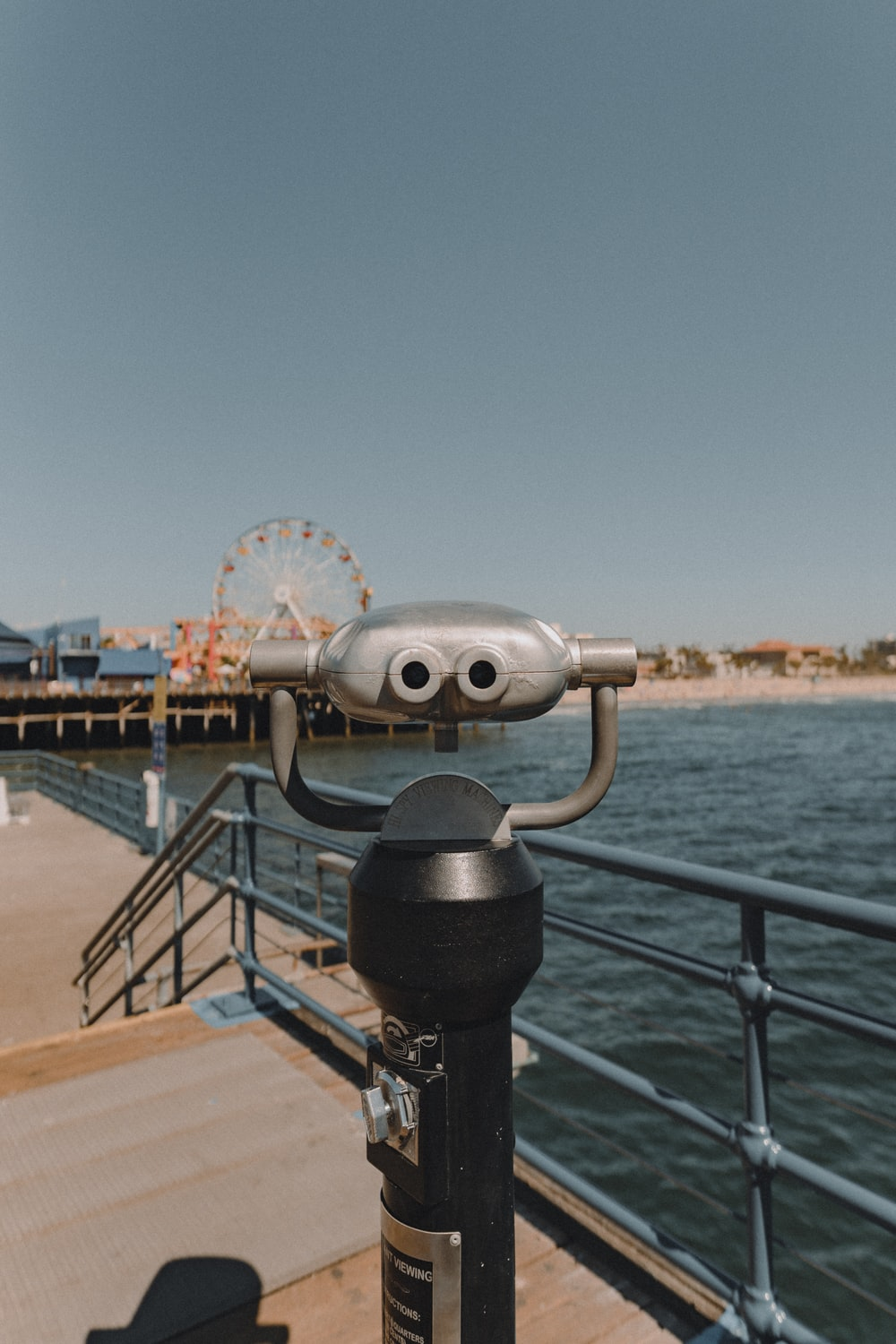 gray and black coin operated telescope on dock during daytime