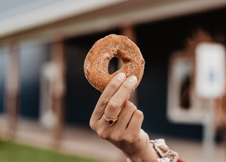 person holding doughnut during daytime