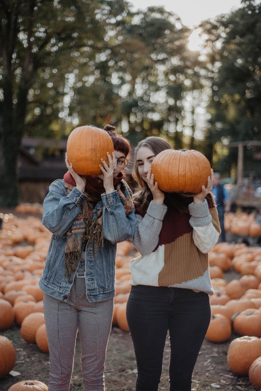 woman in blue denim jacket holding pumpkin during daytime