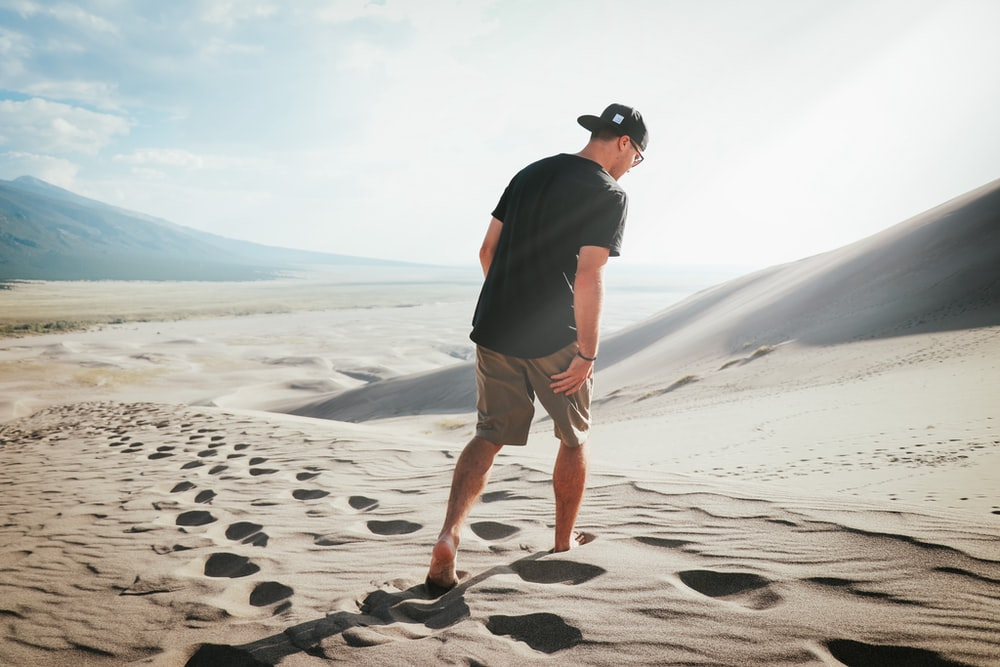 man in black t-shirt and brown shorts standing on gray sand during daytime