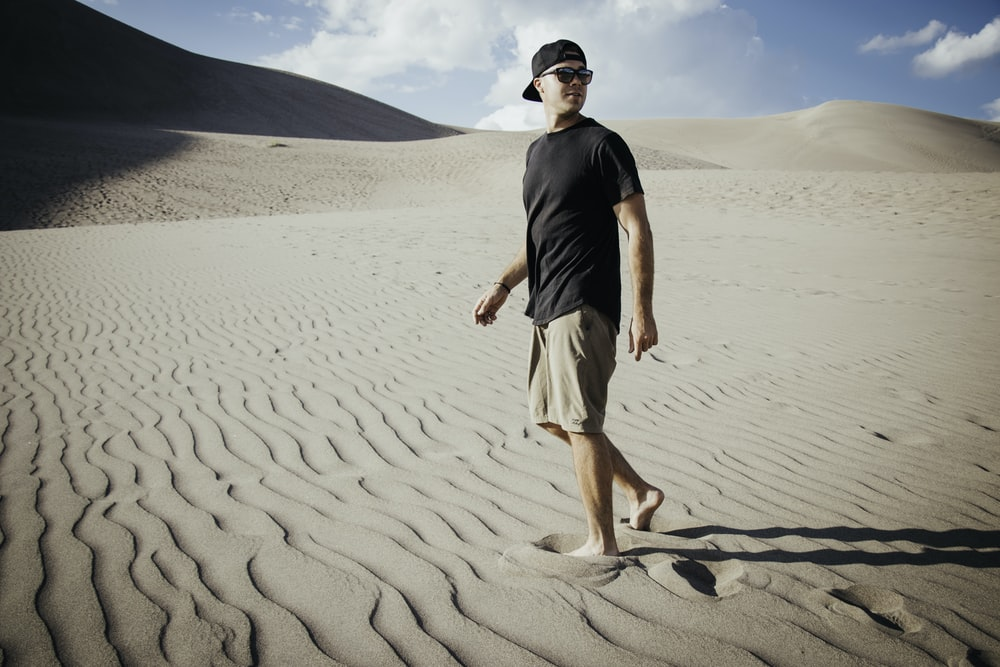 man in black crew neck t-shirt and white shorts standing on brown sand during daytime