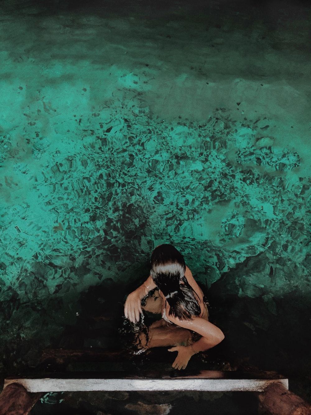 woman in black bikini top swimming on water