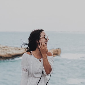 woman in white crew neck t-shirt covering her face with her hand