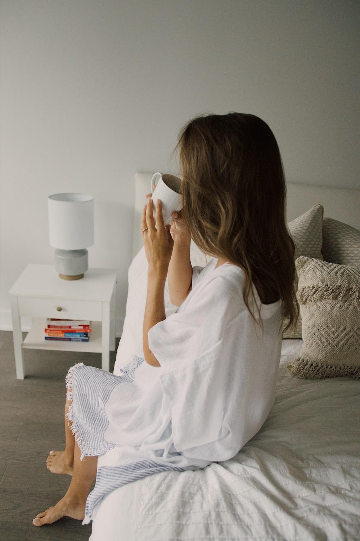 woman in white robe drinking from white ceramic mug