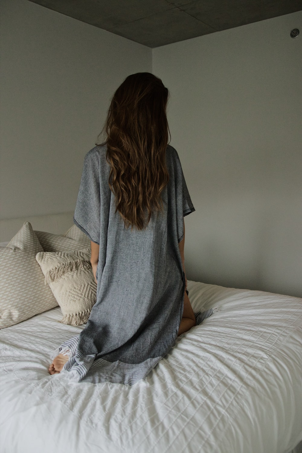 woman in gray robe sitting on bed