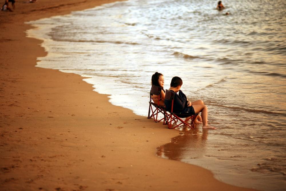 2 boys sitting on black folding chair on beach during daytime