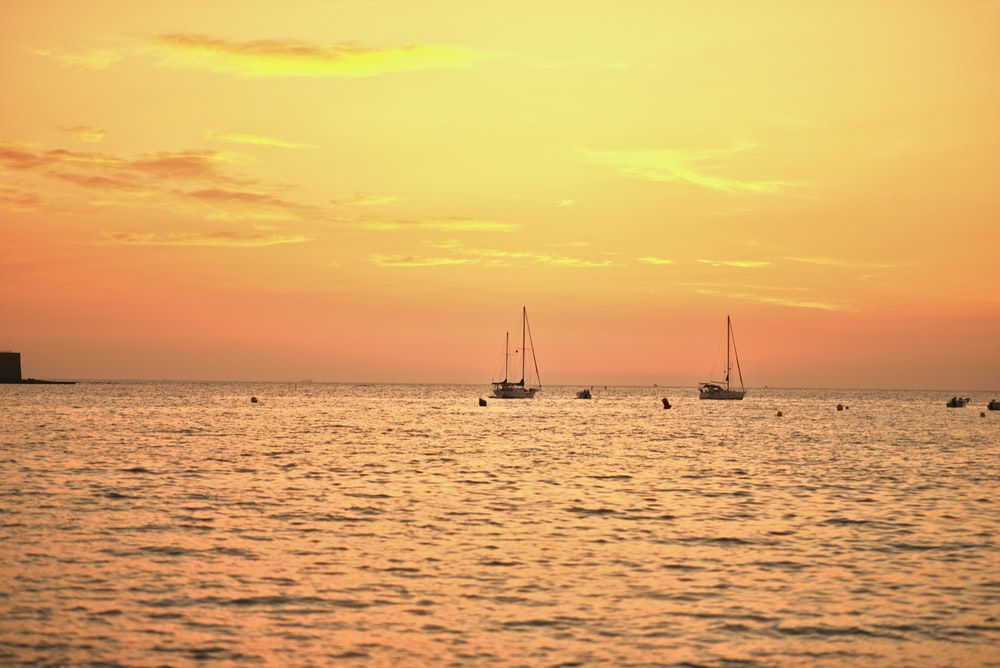 silhouette of 2 sail boats on sea during sunset