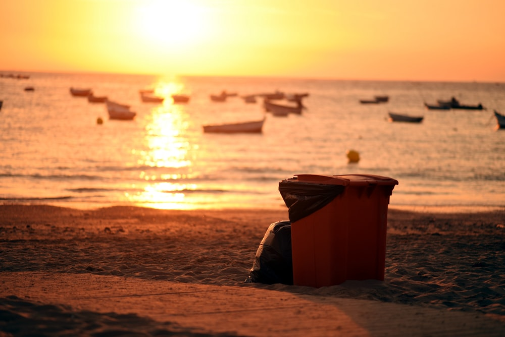 brown plastic bucket on beach shore during sunset