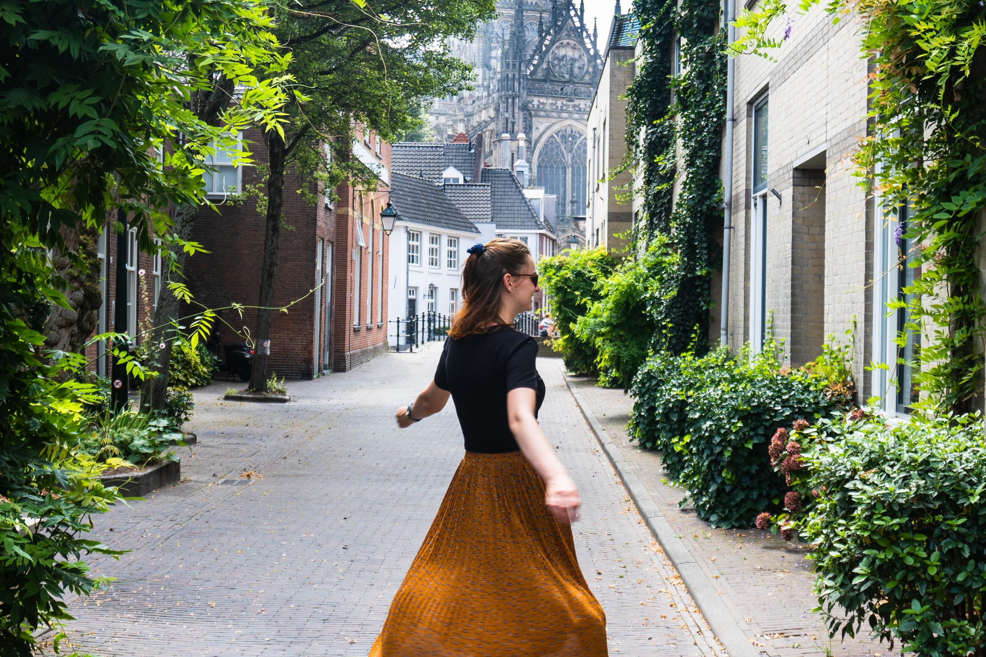 woman in black long sleeve shirt and red skirt walking on sidewalk during daytime