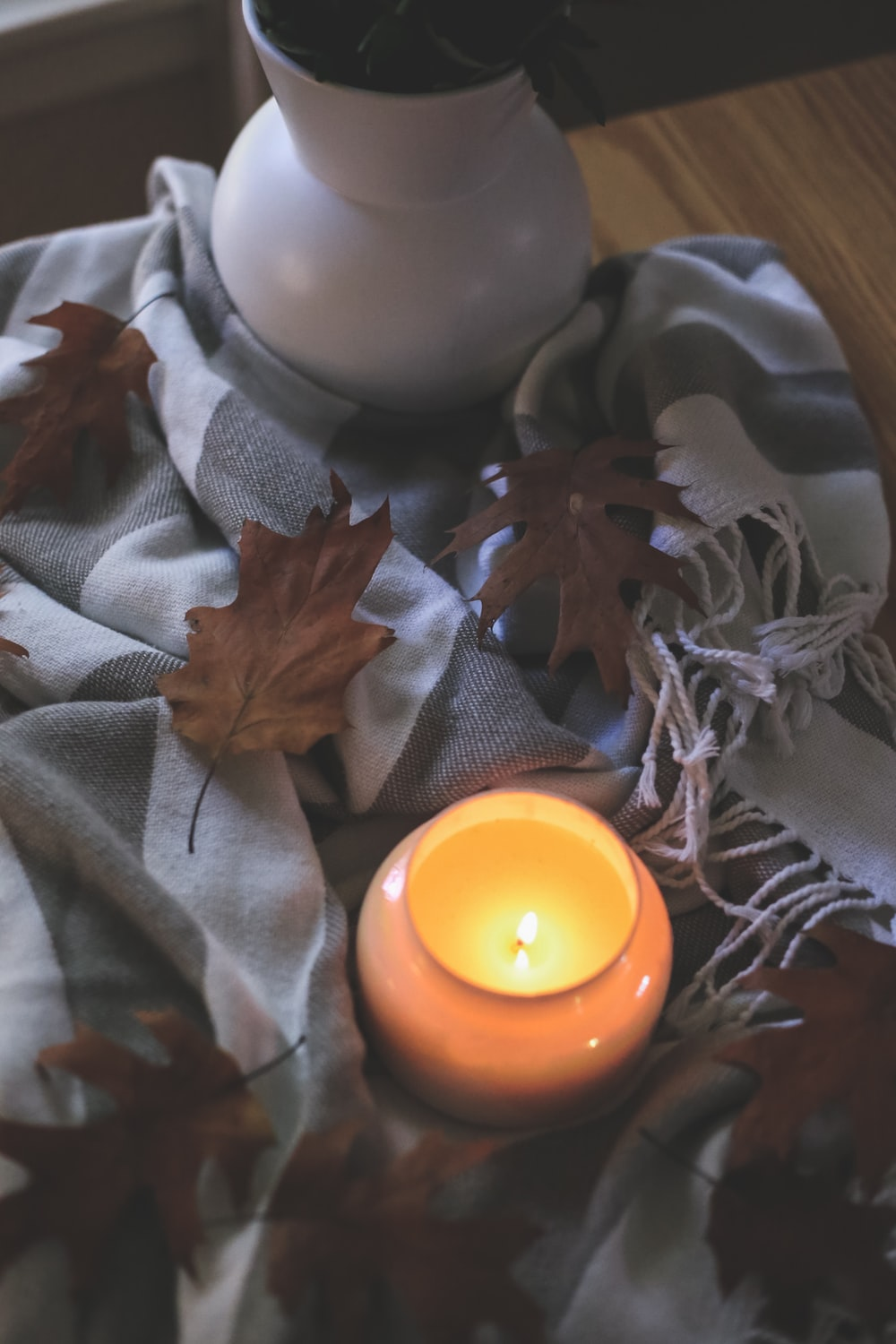 white and yellow candle on gray and brown floral textile