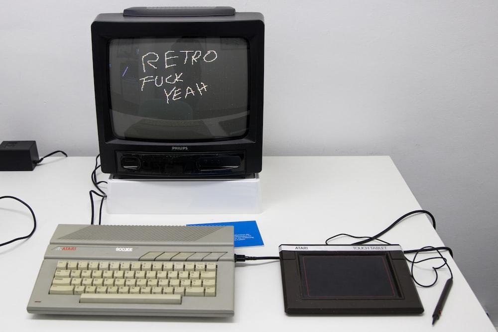 black crt tv beside white computer keyboard