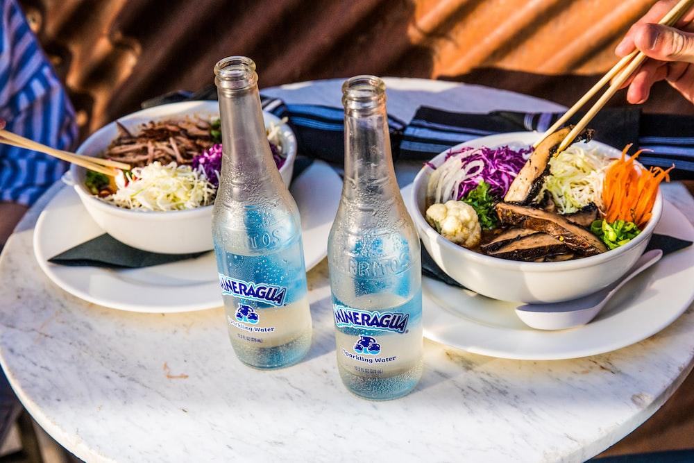 2 blue glass bottles on white table