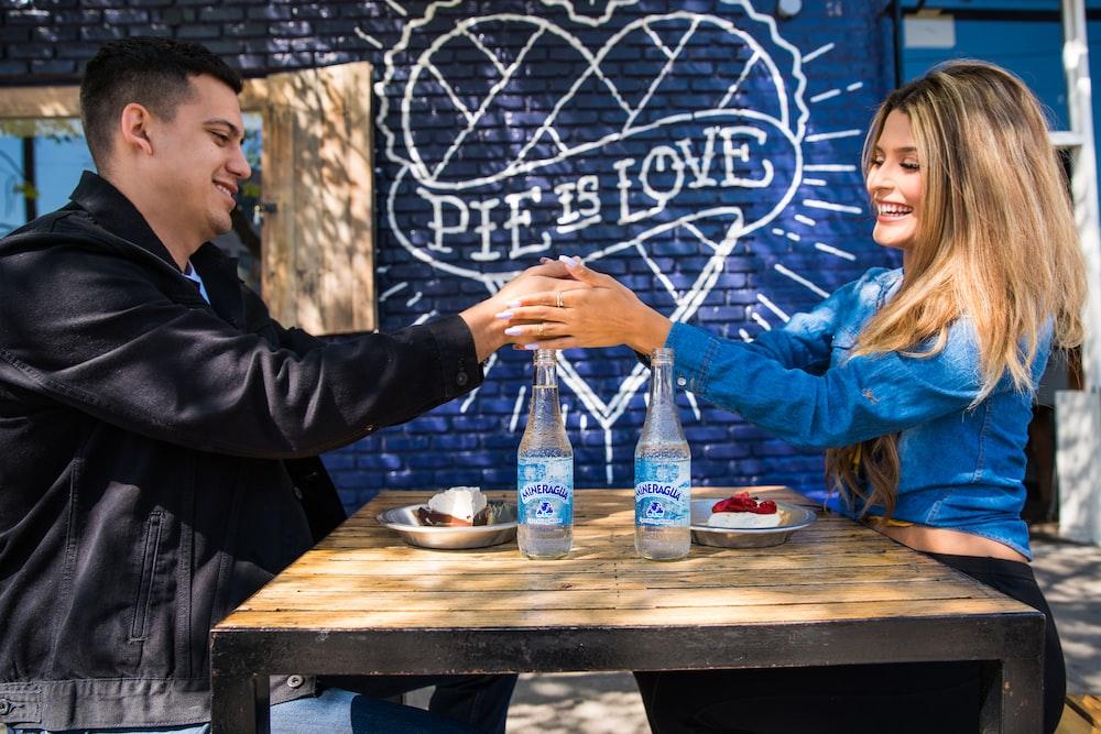 man in black jacket sitting beside woman in blue jacket