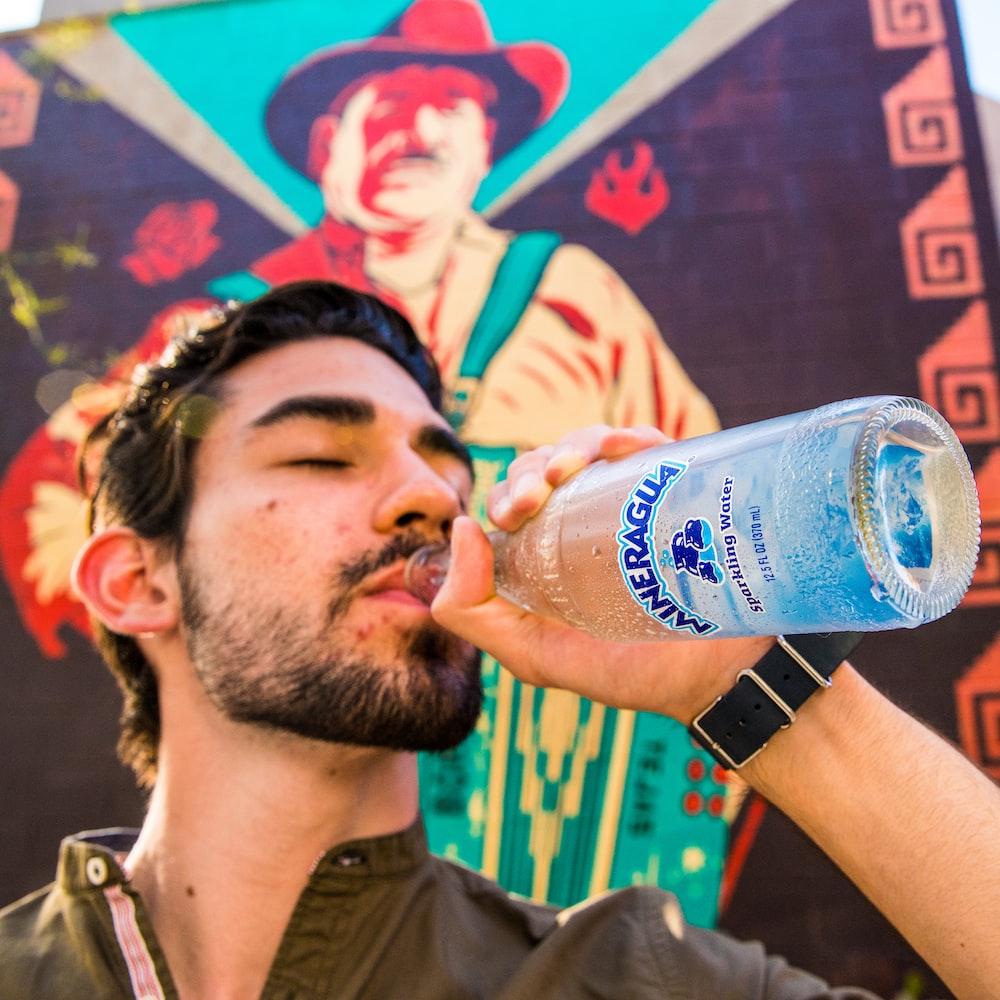 man in black crew neck t-shirt drinking pepsi bottle
