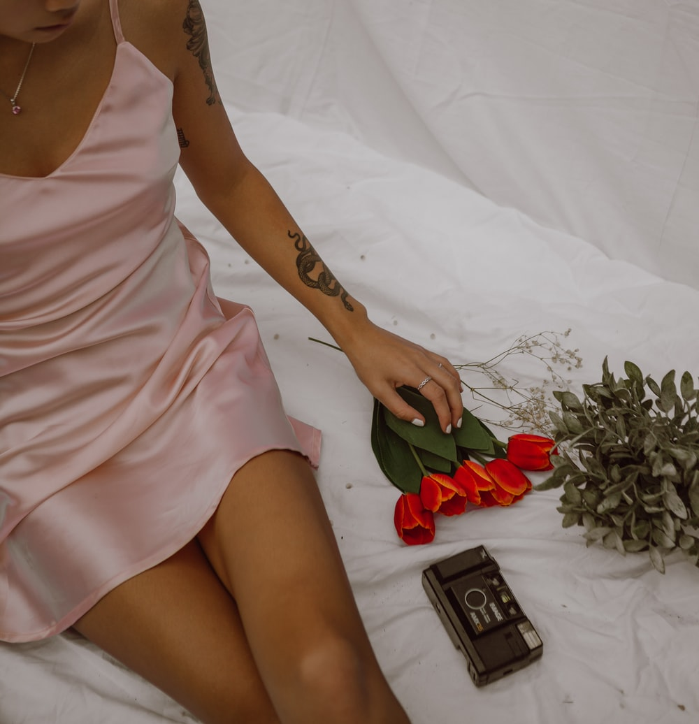 woman in pink spaghetti strap dress holding red rose