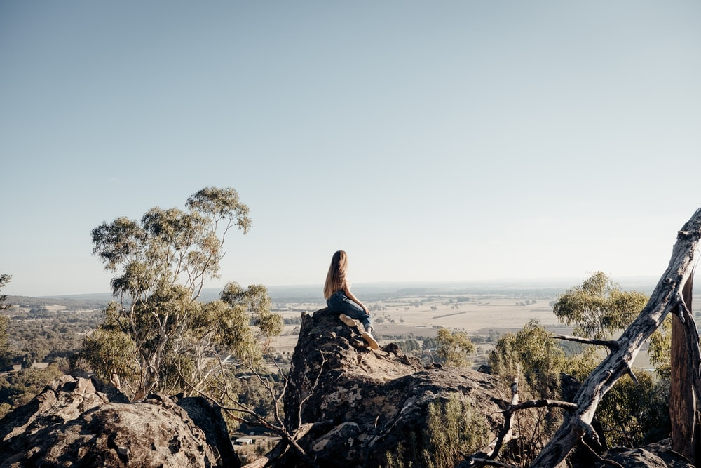 woman sitting on rock formation during daytime