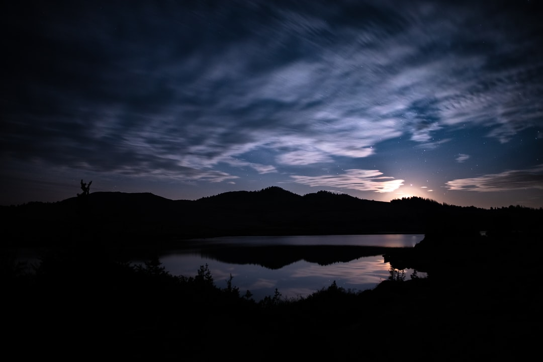 Silhouette of Mountain Near Body of Water During Night Time - unsplash