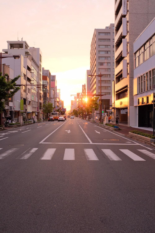gray asphalt road in between of brown concrete buildings during daytime