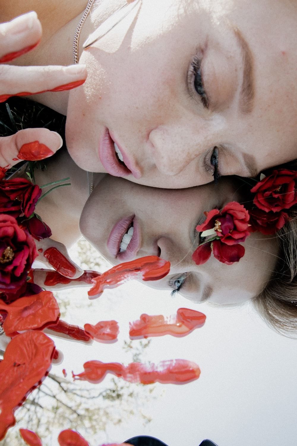 woman with red petals on her face