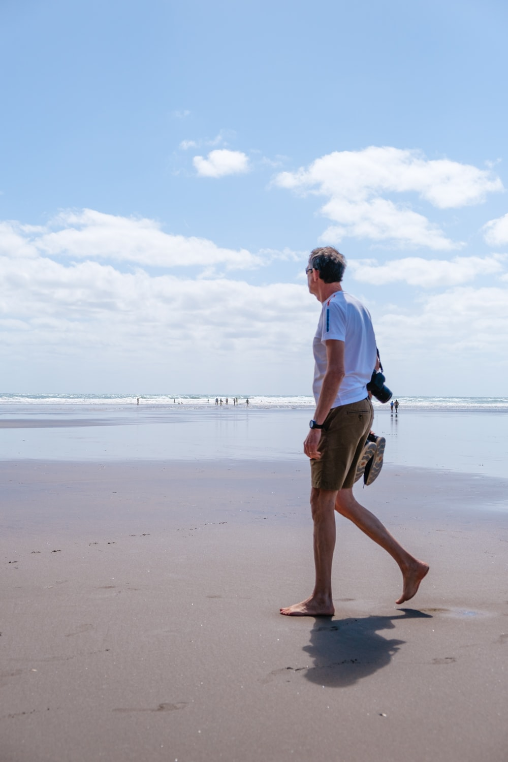 man in white shirt and brown shorts holding black and white dog on beach during daytime