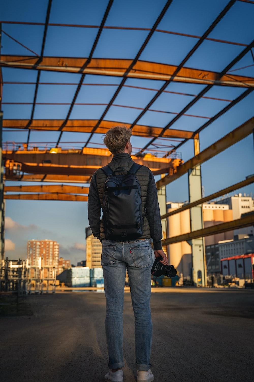 man in black jacket and blue denim jeans standing on sidewalk during daytime