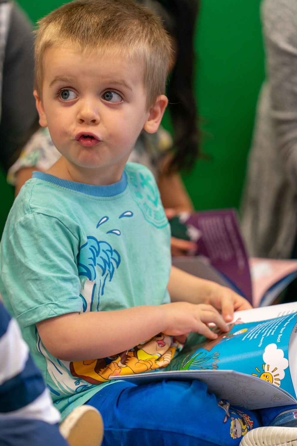 boy in green crew neck t-shirt holding book