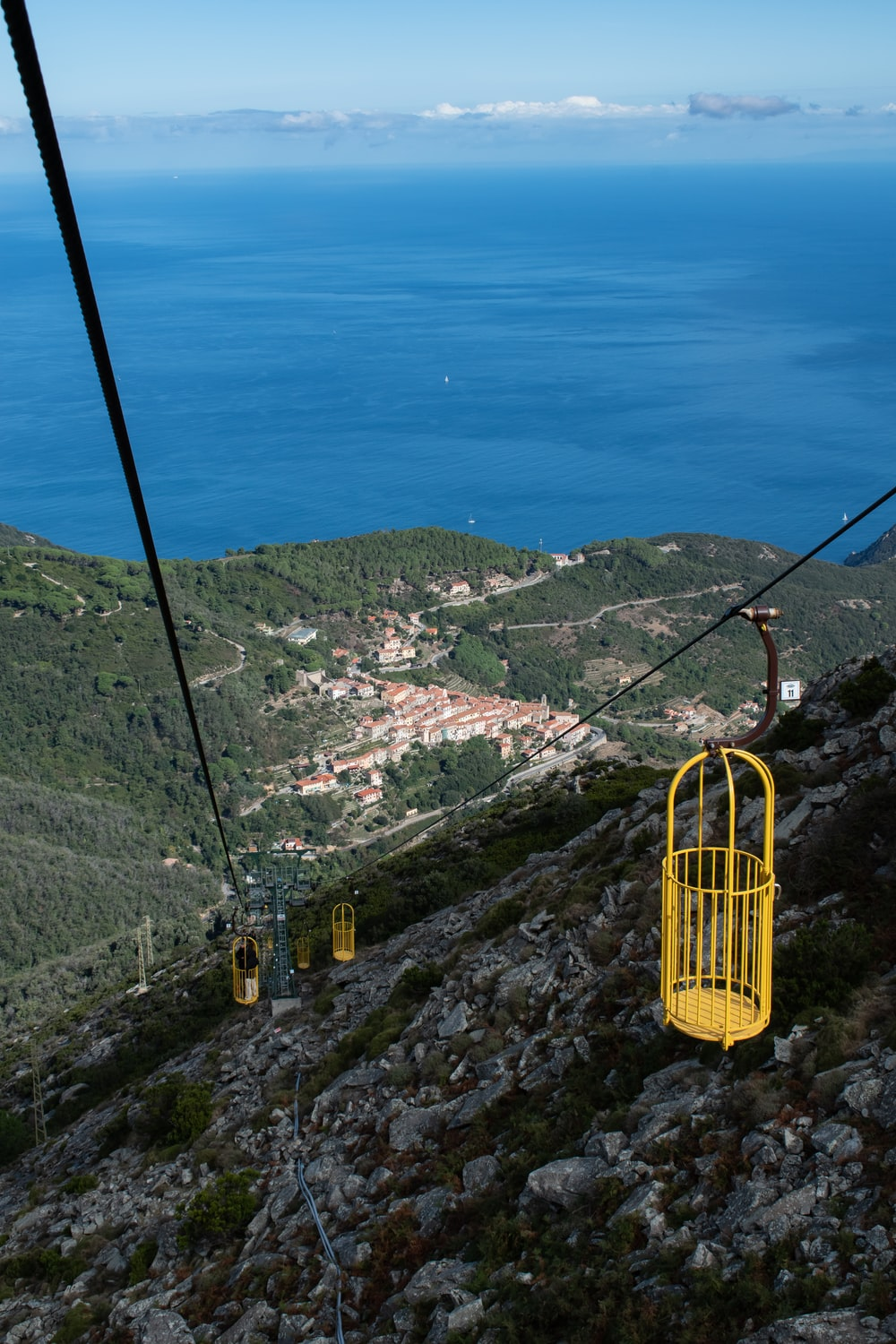yellow cable car over green trees and mountains during daytime