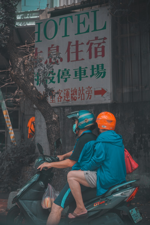 man in red t-shirt and orange helmet sitting on motorcycle