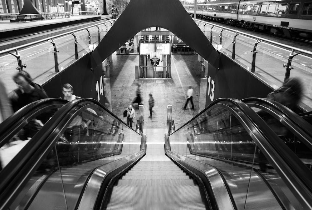 grayscale photo of people walking on escalator