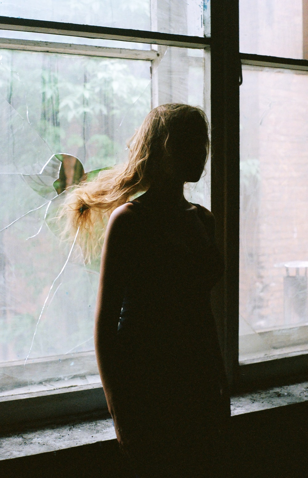 woman in black tank top standing beside window