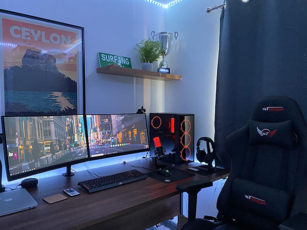 茶色の木製の机の上の黒いフラットスクリーンコンピューターモニター