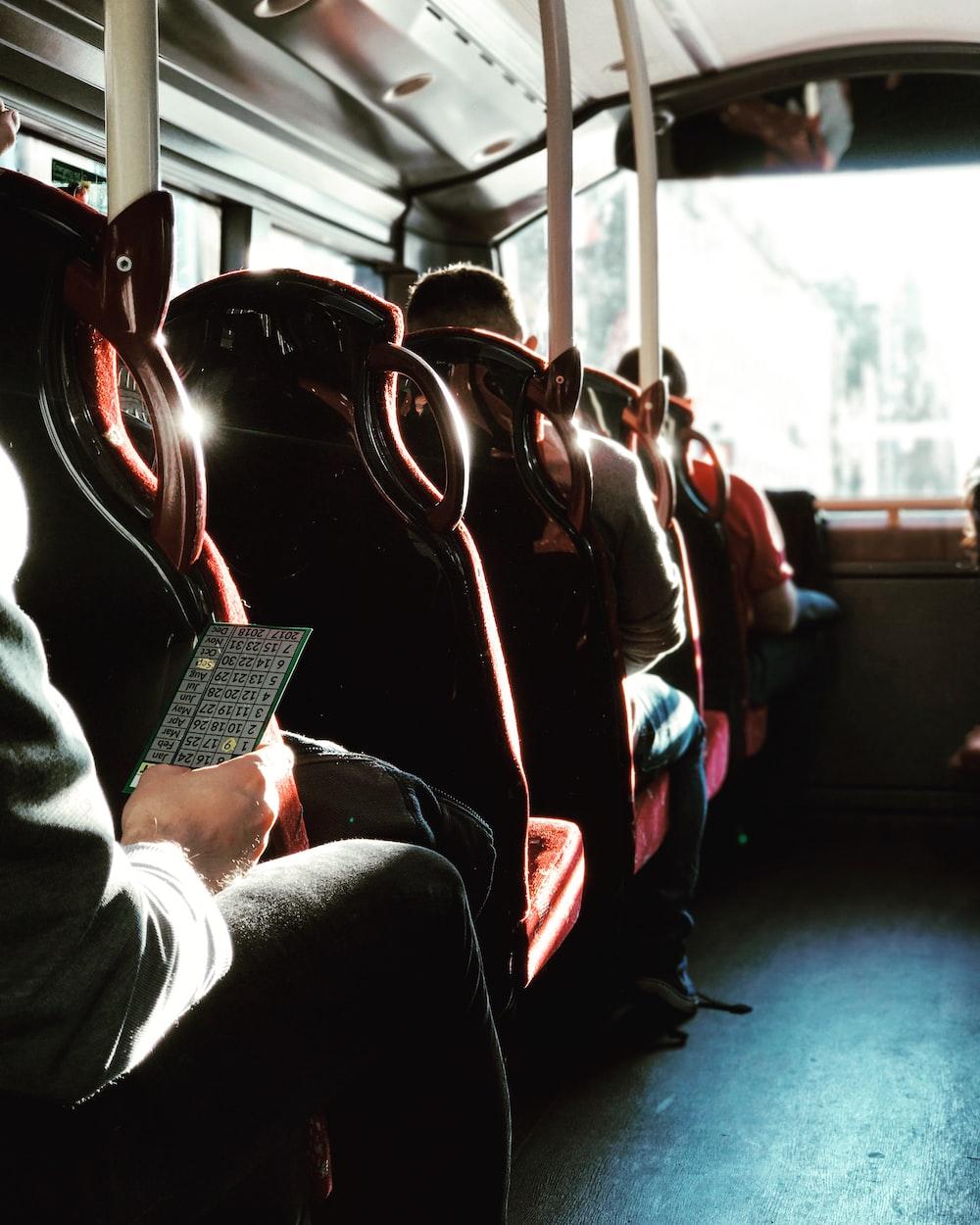 man in black jacket sitting on bus seat